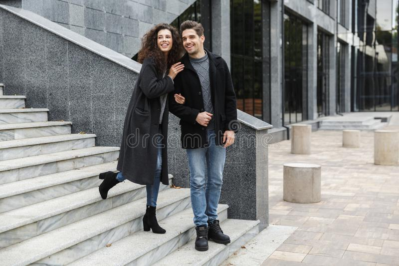 Full length image of stylish couple man and woman 20s in warm clothes, walking down gray stairs outdoor. Full length image of stylish couple men and women 20s in royalty free stock photography