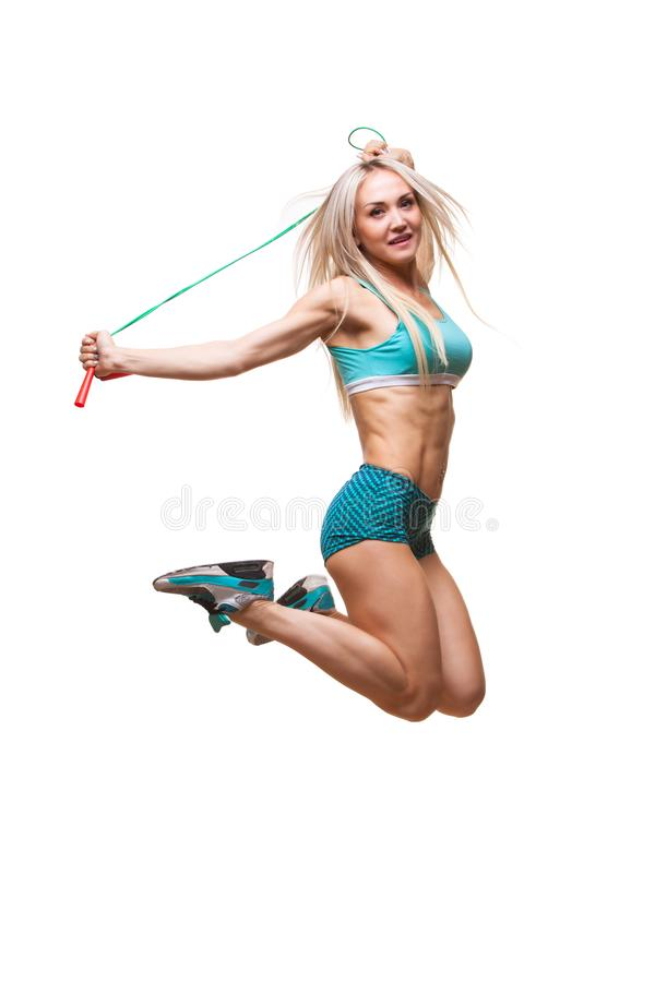 Full length image of a young sports woman jumping on skipping rope over white background stock photography