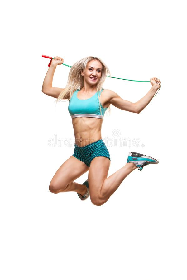 Full length image of a young sports woman jumping on skipping rope over white background stock images