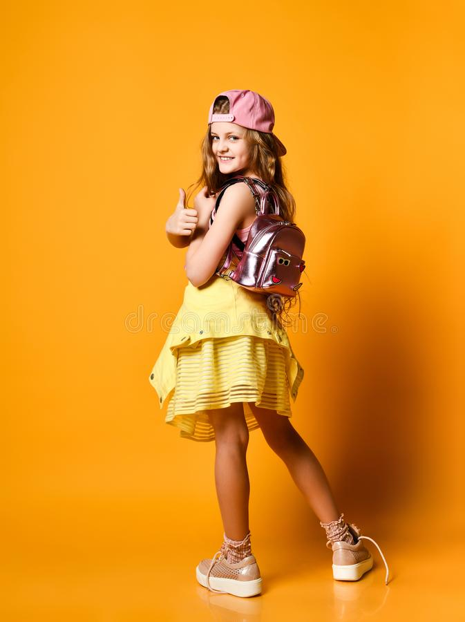 Full-length indoor portrait of a teenager girl in a yellow skirt. sneakers and a cap with a glamorous backpack. stock photography