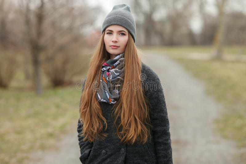 Full length lifestyle portrait of young and pretty adult woman with gorgeous long hair posing in city park with shallow depth of f royalty free stock photography