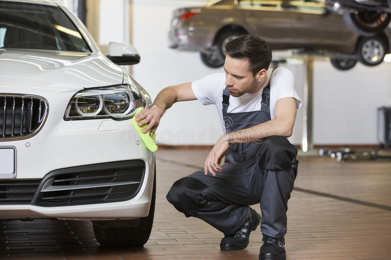 Full length of maintenance engineer cleaning car in workshop stock images