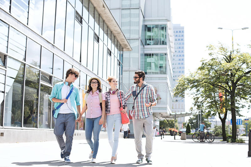 Full-length male and female friends walking on city street stock photo