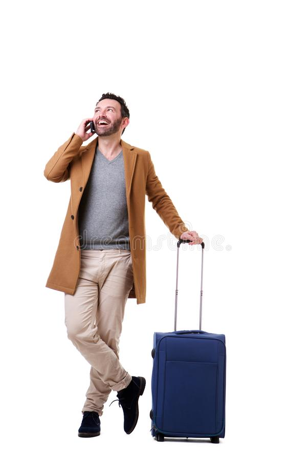 Full length male traveler talking with mobile phone against white background stock photos
