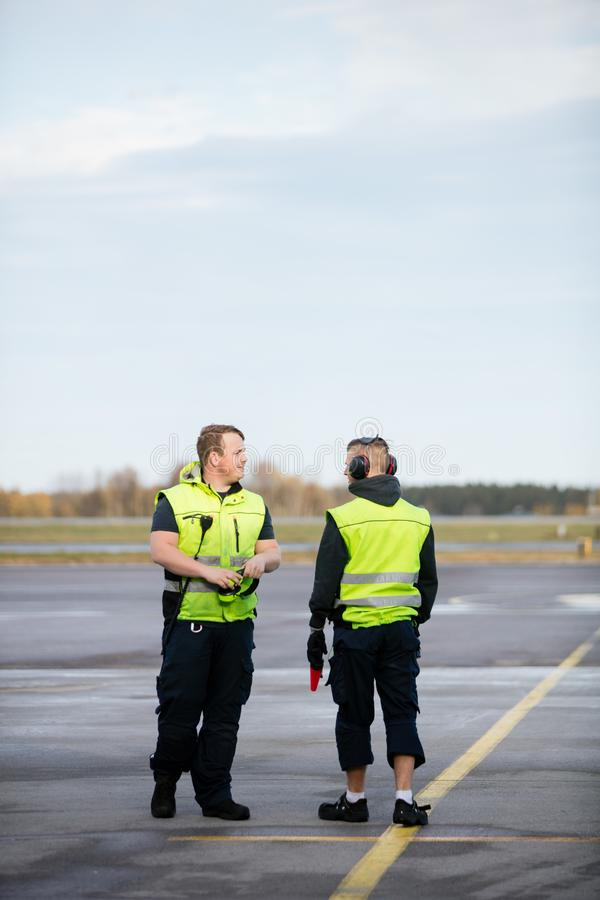 Workers In Reflective Jackets Standing On Airport Runway. Full length of male workers in reflective jackets standing on airport runway royalty free stock photos