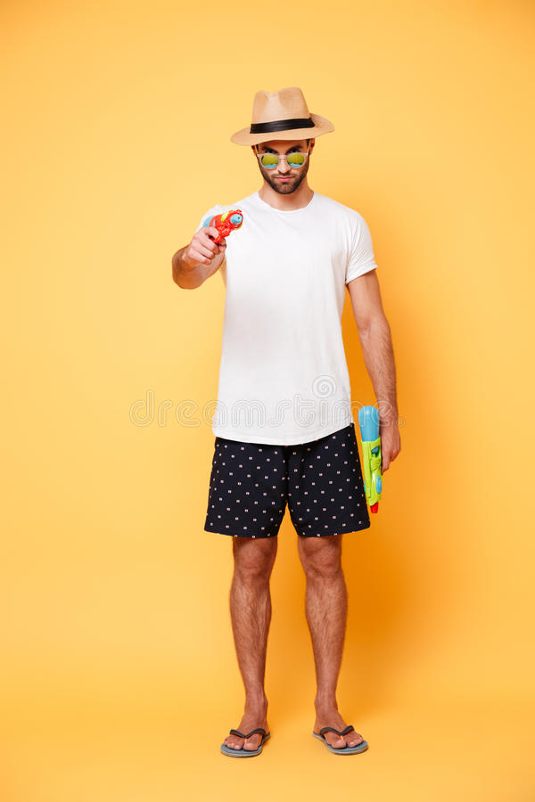 Full-length man aiming with water gun. Full-length young bearded serious man in sunglasses aiming with water gun isolated stock photo