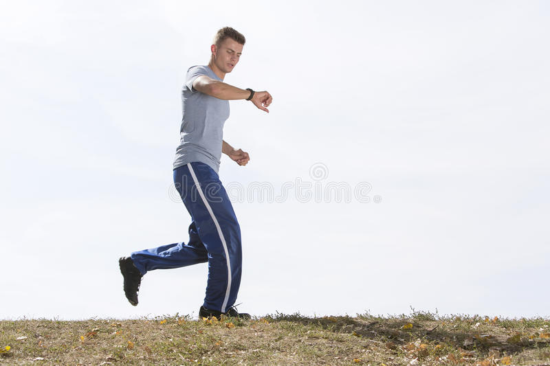 Full length of man checking time while jogging against sky stock image
