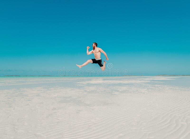 Full Length of a Man Jumping from Beach royalty free stock photo