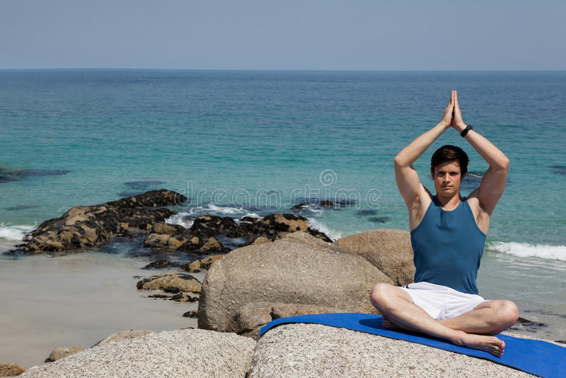 Full length of man meditating at beach. Full length of man meditating while sitting on exercise mat at beach stock photos