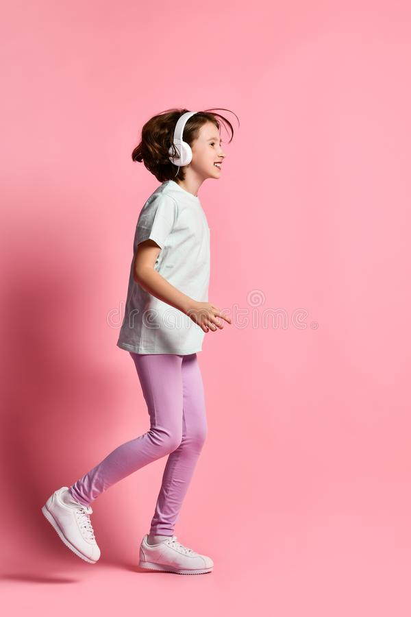 Full-length  girl of music listens in white headphones, enjoying the pleasure of listening to music against a pink background stock images