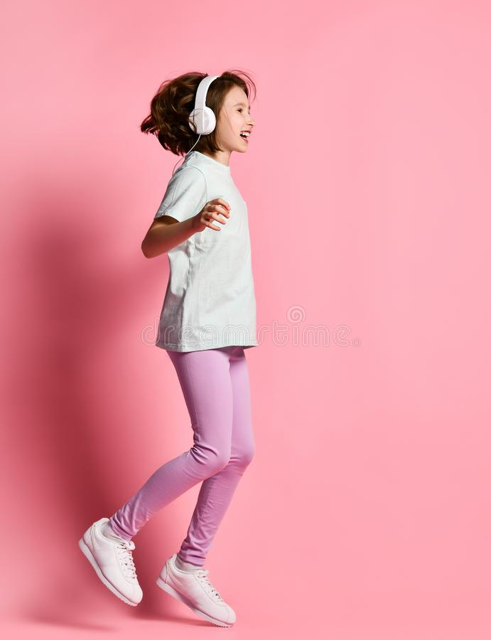 Full-length girl of music listens in white headphones, enjoying the pleasure of listening to music against a pink background stock photos