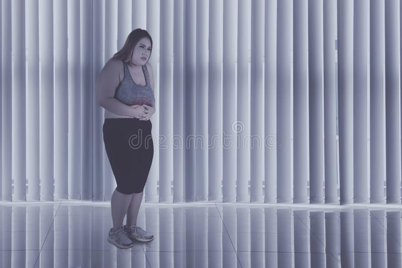 Obese woman suffers from abdominal pain at home. Full length of obese woman wearing sportswear while suffering from abdominal pain in the dark room royalty free stock photography
