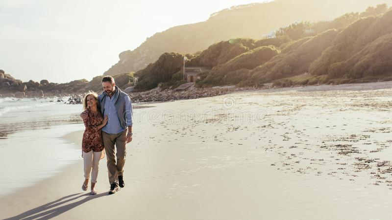 Senior couple strolling on the beach stock images