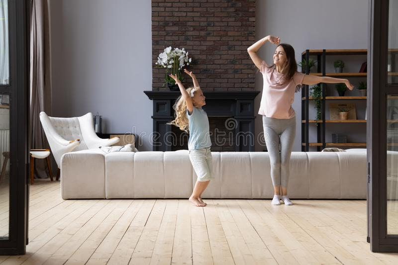 Overjoyed young mother dancing with little cute adorable smiling daughter. stock images
