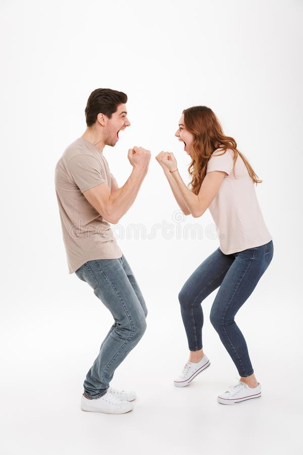 Full length photo of attractive active couple guy and girl wearing beige t-shirts expressing delight standing face to face and cl. Enching fists over white stock photography