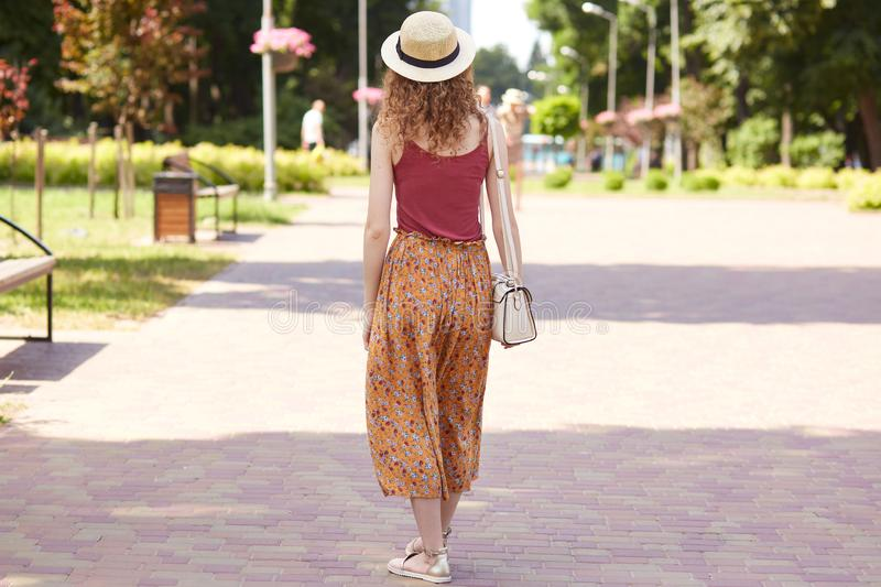 Full length photo from back view of young slender lady walking in tree shadow, fond of nature, spending lunchtime in recreation stock photos