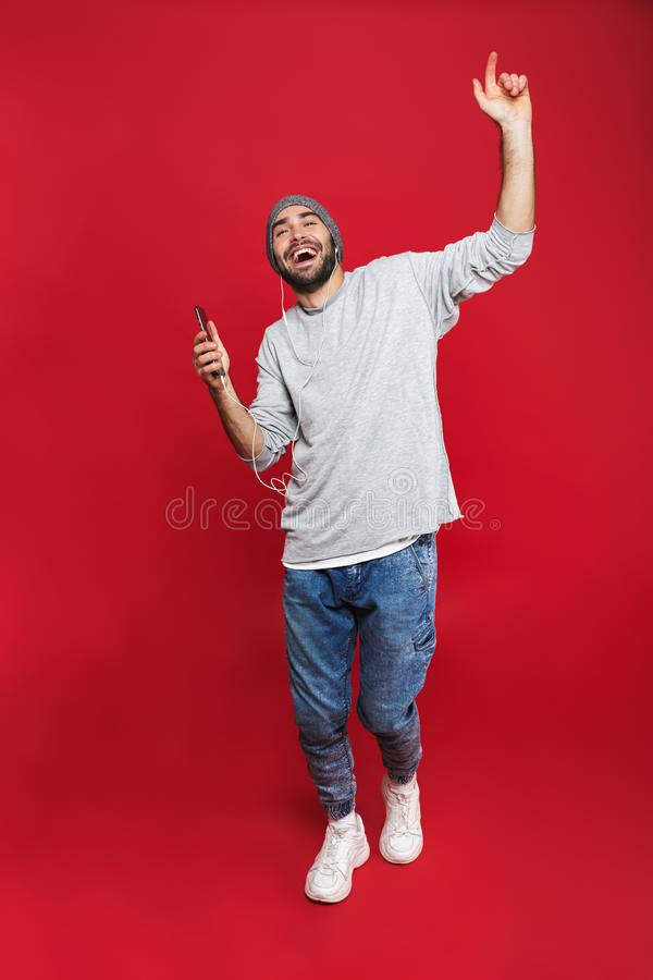 Full length photo of bearded man 30s singing while listening to music with earphones and mobile phone, isolated over red royalty free stock photo