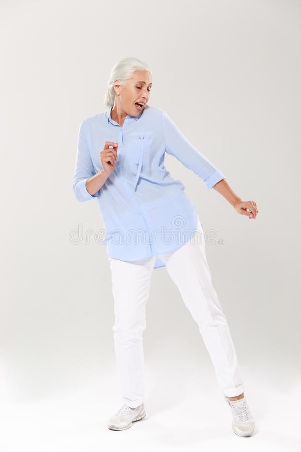 Full-length photo of beautiful old lady, dancing and singing. Over white background royalty free stock image