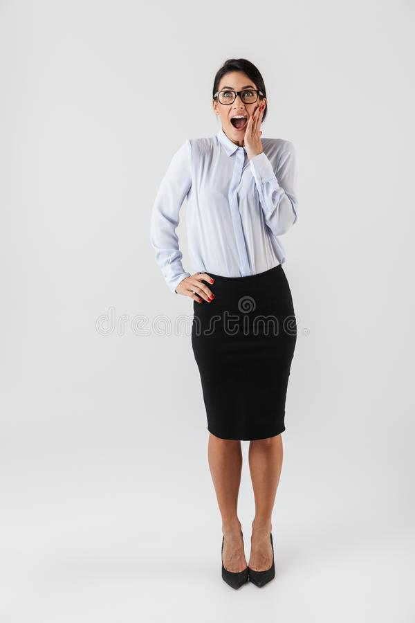Full length photo of businesslike woman wearing eyeglasses standing in the office, isolated over white background. Full length photo of businesslike woman stock images