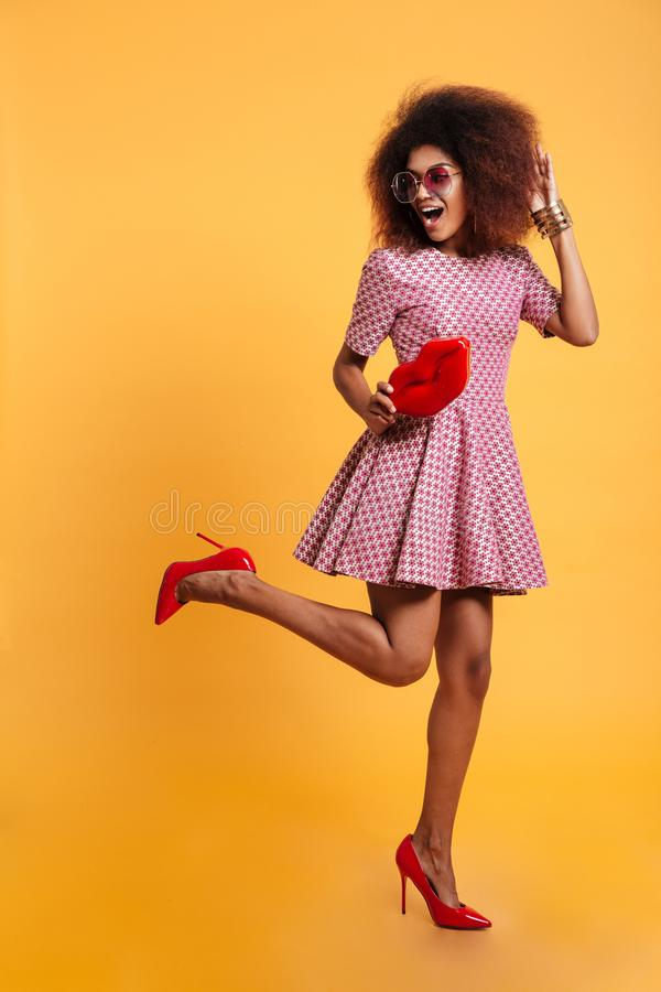 Full length photo of charming african retro stylish woman in dress and high heels standing on one leg while posing with big red l stock photo