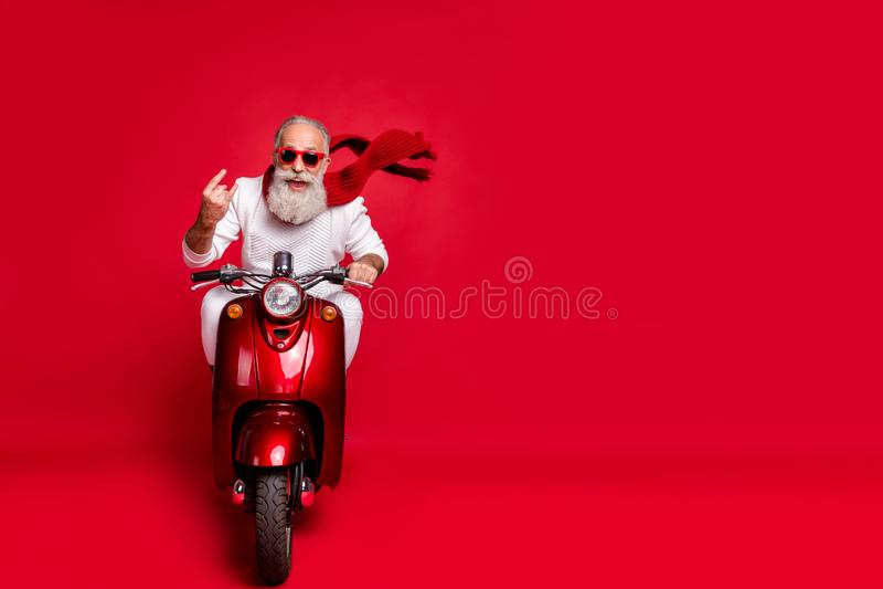 Full length photo of cheerful old man in eyewear eyeglasses showing rocker sign driving his bike wearing white sweater stock photos