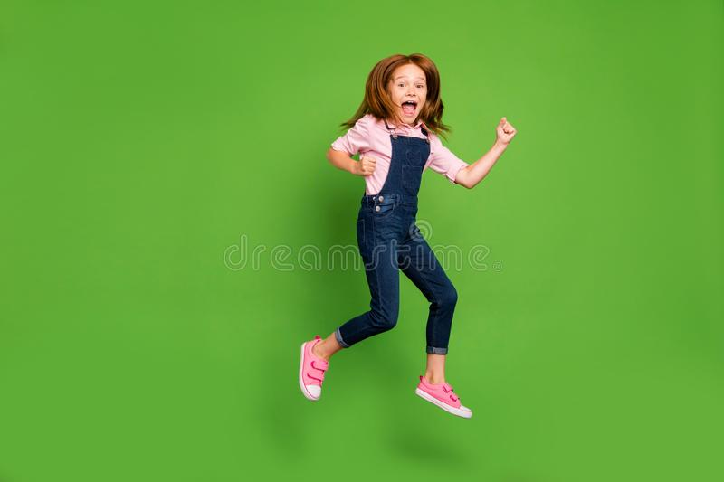 Full length photo of cheerful pretty little schoolchild jumping high rejoicing summer holidays start wear casual denim. Full length photo of cheerful pretty royalty free stock images