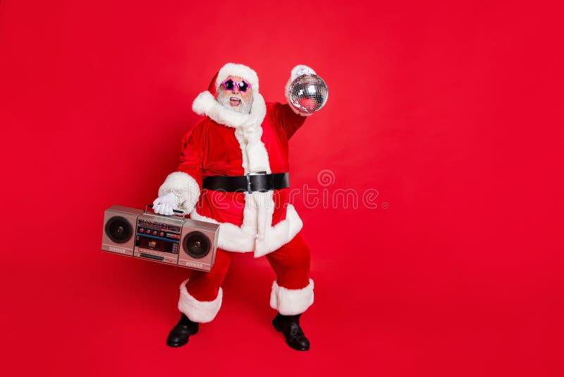 Full length photo of cheerful santa claus in headwear hat holding boom box glittering ball dancing on newyear party. Full length photo of cheerful santa claus in royalty free stock photography