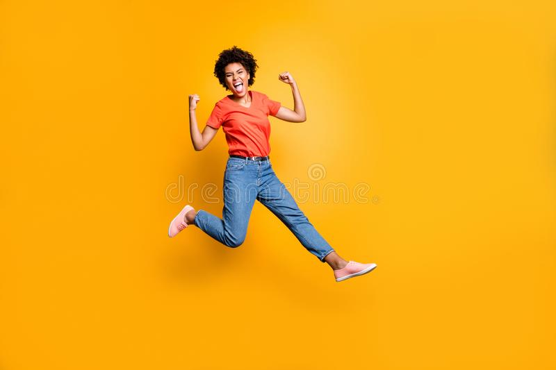 Full length photo of crazy ecstatic girl raise her fists scream shout yeah celebrate victory lottery discounts jump wear. Red t-shirt trendy, denim jeans royalty free stock images
