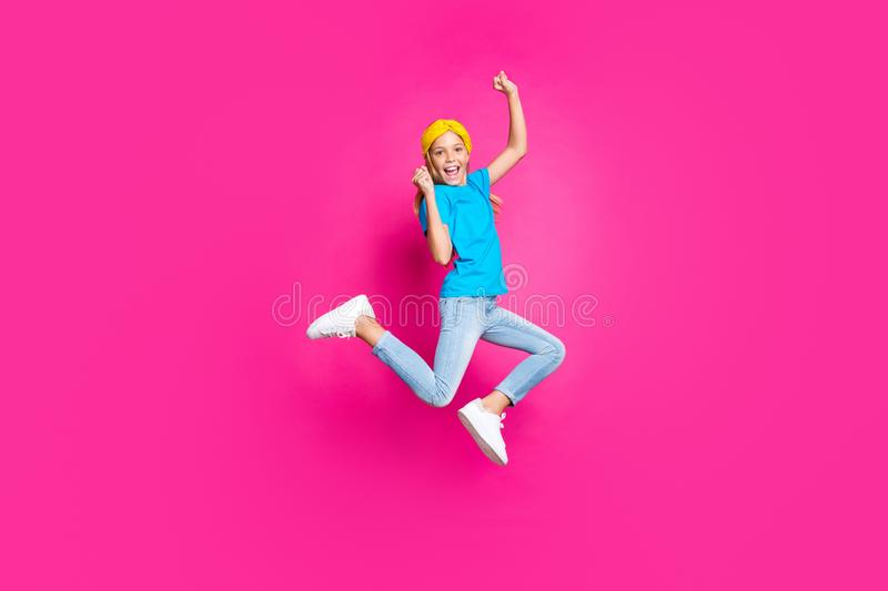 Full length photo of crazy funny kid raise fists scream yeah jump ecstatic see incredible discounts for spring vacations. Full length photo of crazy funny kid stock photography
