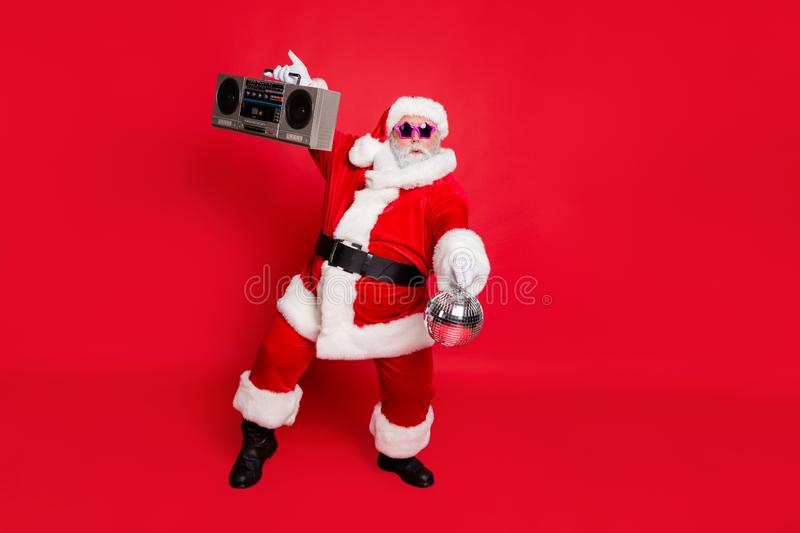 Full length photo of cute santa claus hold style sound boom box glittering ball dancing on noel party wear eyeglasses. Full length photo of cute santa claus hold royalty free stock images