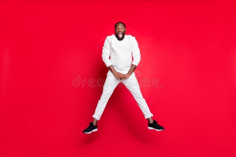 Full length photo of excited dark skin handsome guy jumping high rejoicing at best x-mas party with buddies wear white. Full length photo of excited dark skin stock photos