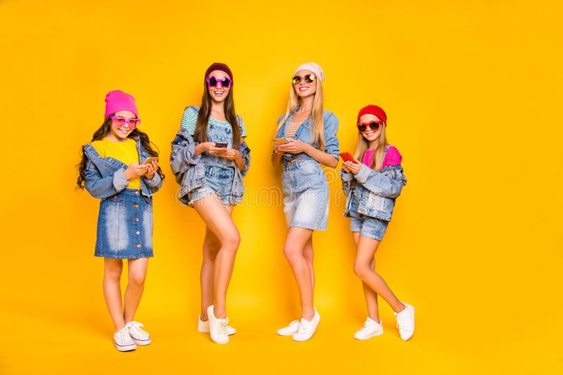 Full length photo of four nice positive cool millennials using modern technology following stars users on social network royalty free stock images