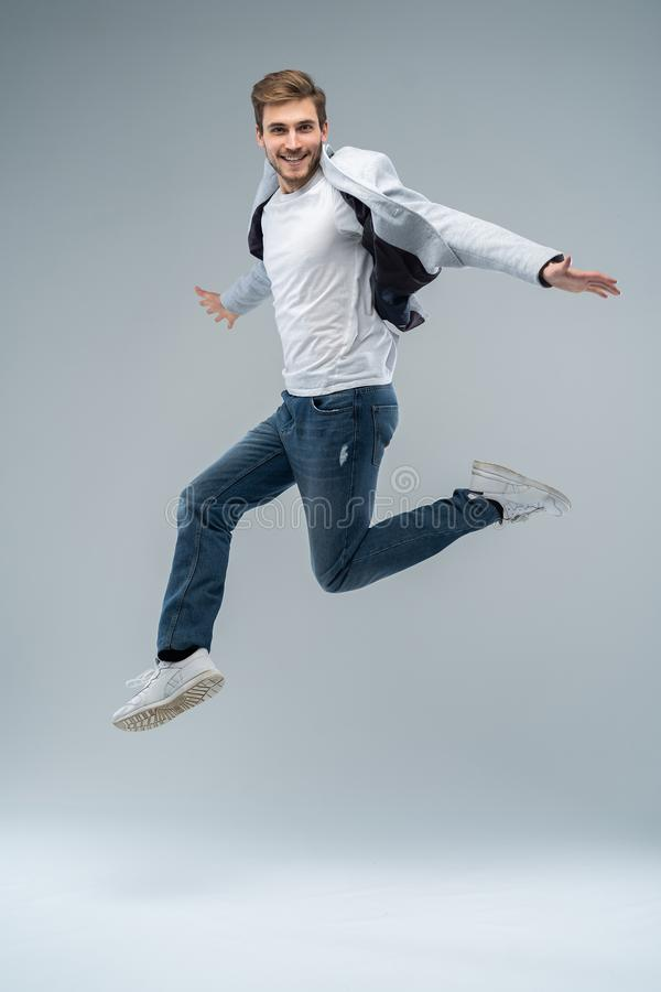 Full-length photo of funny man in casual t-shirt, blazer and jeans running or jumping in air isolated over gray royalty free stock photos