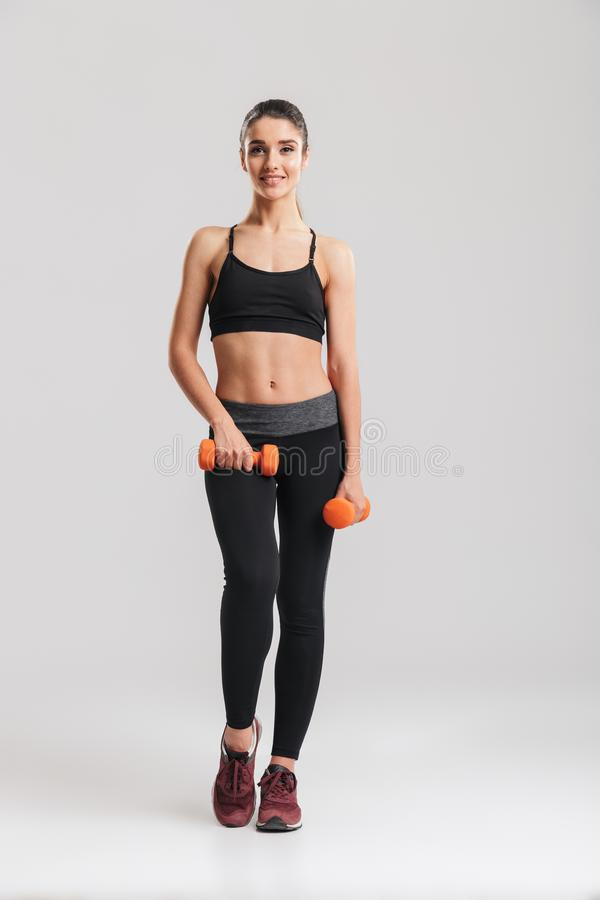Full-length photo of gorgeous slim woman smiling and doing exercises with small dumbbells, isolated over gray background stock photo