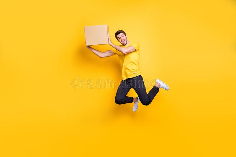 Full length photo of handsome guy jumping high holding big carton box moving to new flat wear casual t-shirt black pants royalty free stock photos