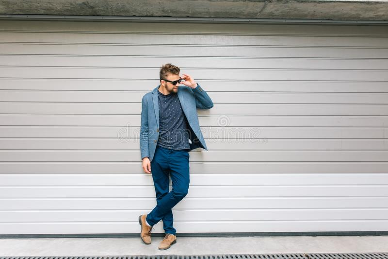 Full-length photo handsome guy posing on gray wall background. He wears gray jacket, T-shirt, jeans, brown shoes. He stock photos