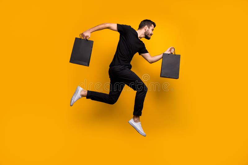 Full length photo of handsome millennial guy jumping high running shopping mall buying new clothes hold bags wear black. Full length photo of handsome millennial royalty free stock images