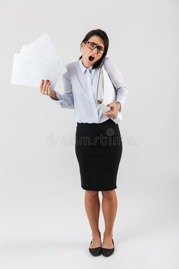 Full length photo of irritated businesswoman wearing eyeglasses holding paper folders in the office, isolated over white royalty free stock photos
