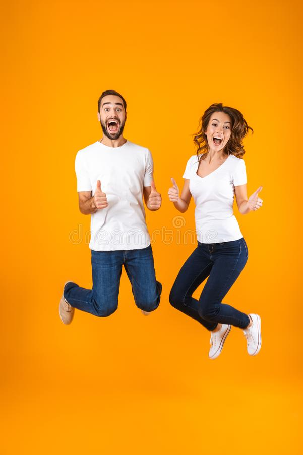 Full length photo of joyful couple screaming in surprise while jumping, isolated over yellow background royalty free stock image