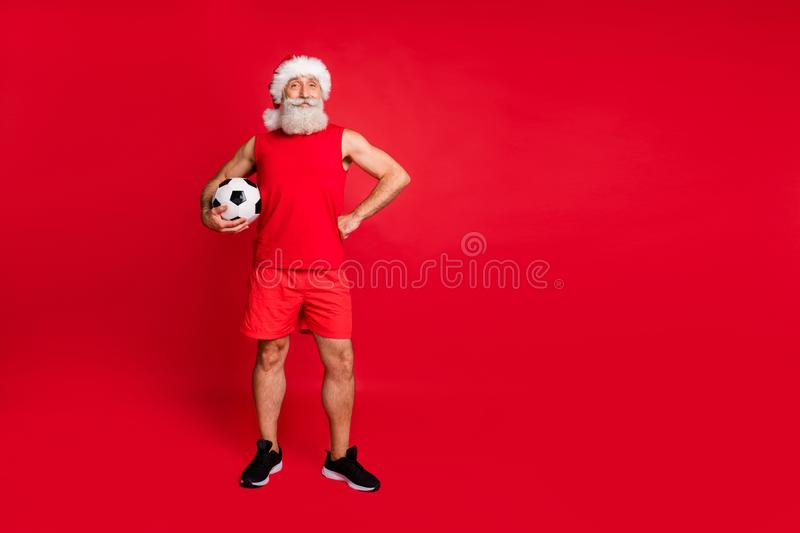 Full length photo of lovely santa claus holding foot ball player wearing sportswear cap panties  over red royalty free stock photos