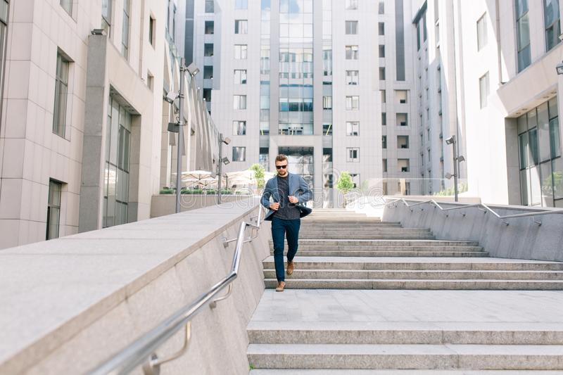 Full-length photo of man in sunglasses walking on concrete stairs on office building background. He wears T-shi.  stock images