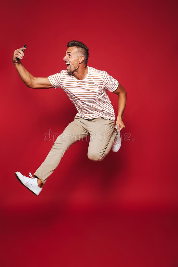 Full length photo of optimistic man in striped t-shirt jumping a royalty free stock photo
