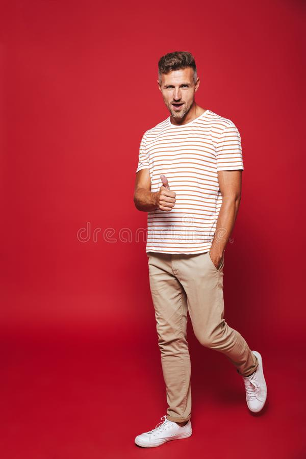 Full length photo of optimistic man in striped t-shirt smiling a stock images