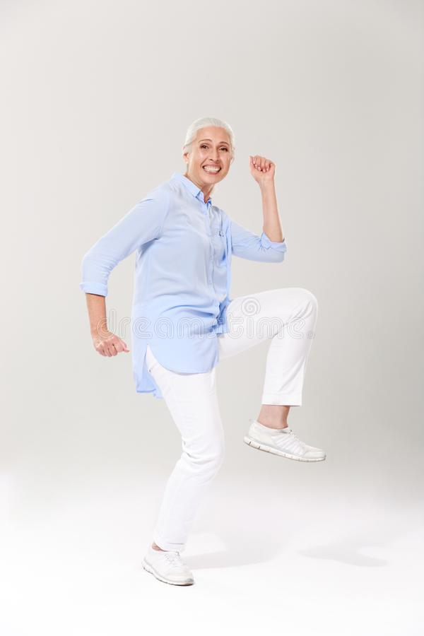 Full-length photo of playful old lady, having fun over white background royalty free stock photography