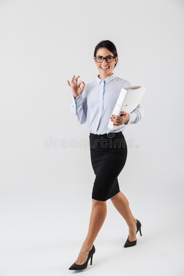 Full length photo of pretty female secretary wearing eyeglasses holding paper folder in the office, isolated over white background. Full length photo of pretty royalty free stock image