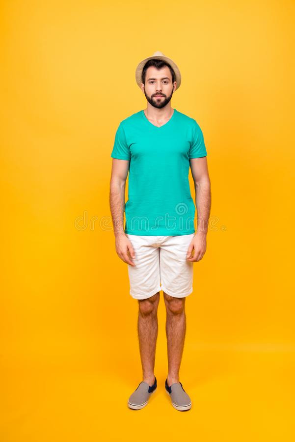 Full length photo of serious confident man wearing casual clothing, he is staying still against vivid yellow background stock photography