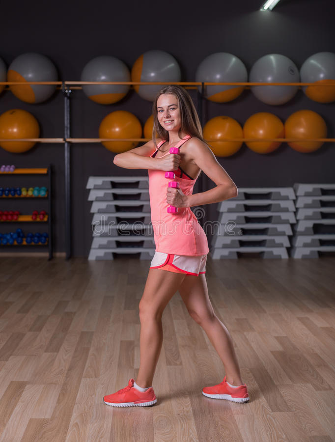 A full-length photo of a young girl with dumbbells exercising on a gym background. A sportive girl in a pink royalty free stock images