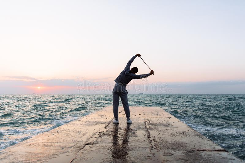 Full length photo of sportsman stretching with skipping rope, near the sea. Full length photo of sportsman practicing exercises, stretching with skipping rope stock image