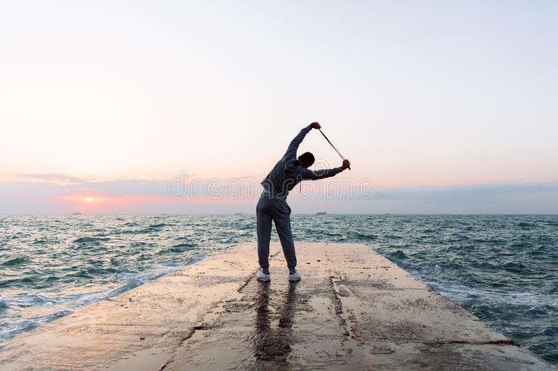 Full length photo of sportsman stretching with skipping rope, near the sea. Full length photo of sportsman practicing exercises, stretching with skipping rope royalty free stock photo