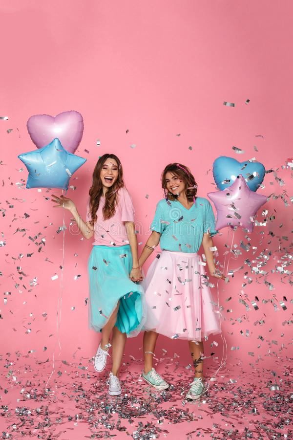 Full length photo of two happy beautiful girls with balloons celebrating birthday party. On pink background royalty free stock photography